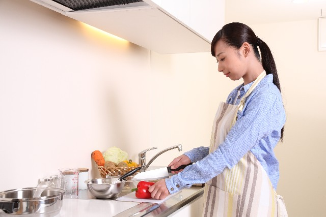 キッチンで料理する主婦