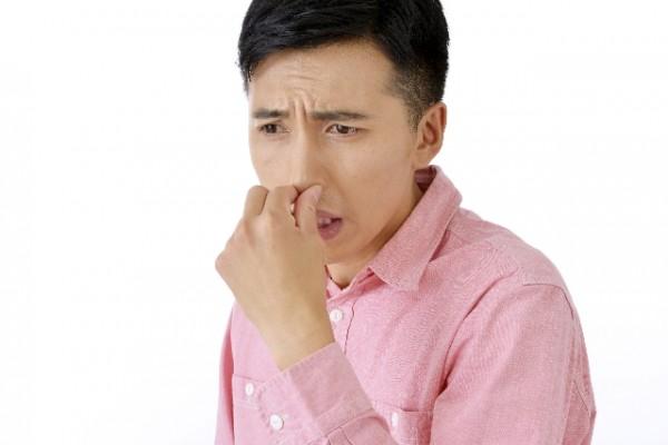 匂いで鼻をつまむ男性