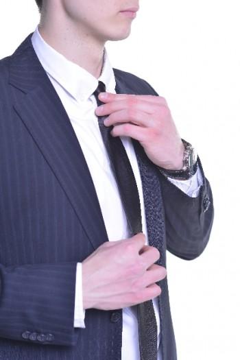 ネクタイを結んで身支度するサラリーマン