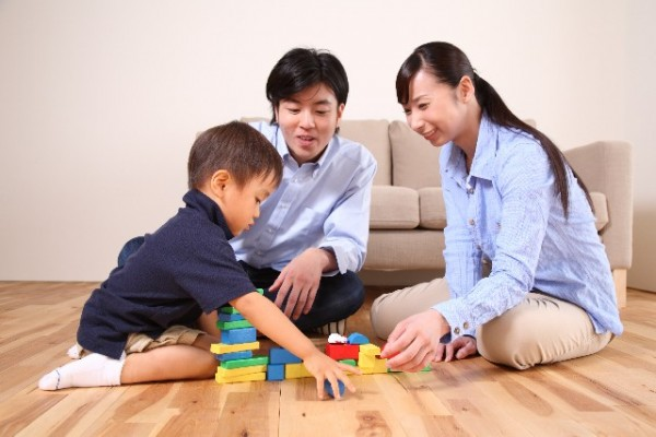 ブロックのおもちゃで遊ぶ家族