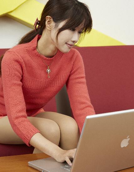 イスに座ってノートパソコンを使う女性