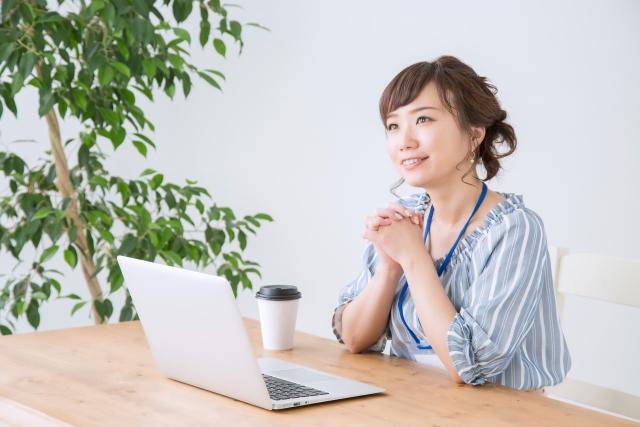 ノートパソコンとデスクに座る女性