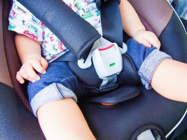 車のチャイルドシートに座る赤ちゃん